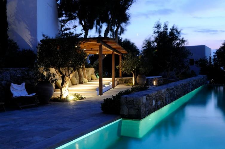 lamp illuminated pool porch with wooden sunbed