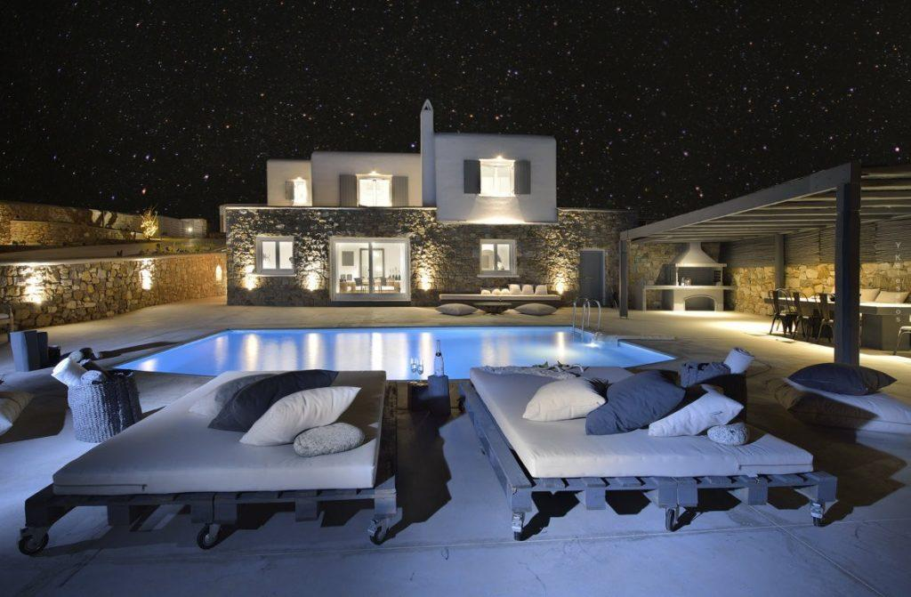 outdoor area with lit villa walls and illuminated pool