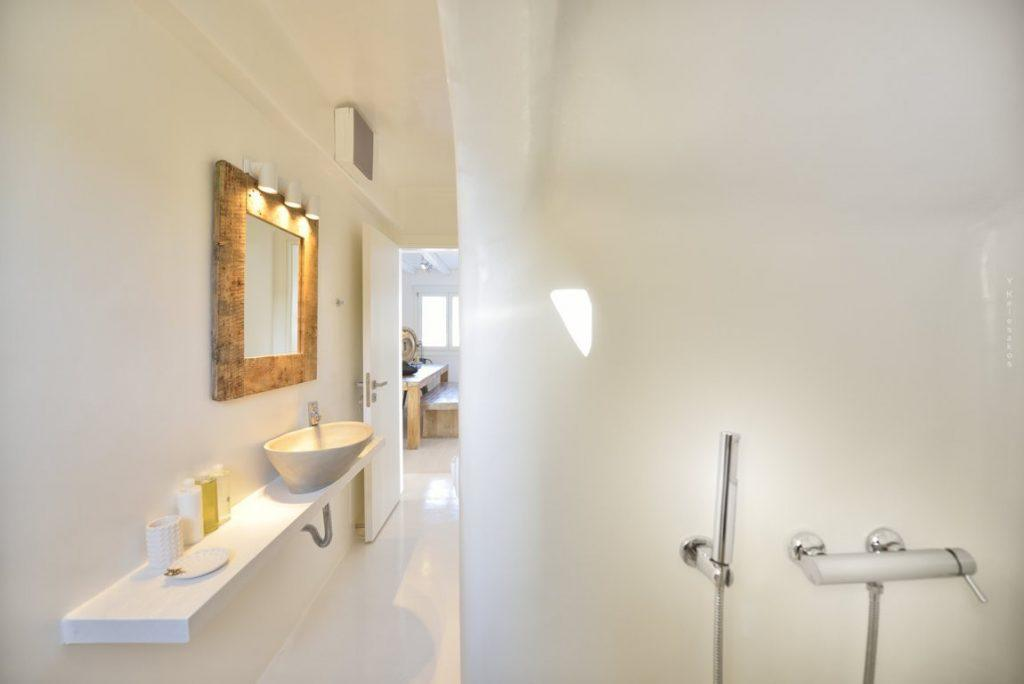 white wall bathroom with lit mirror and shower