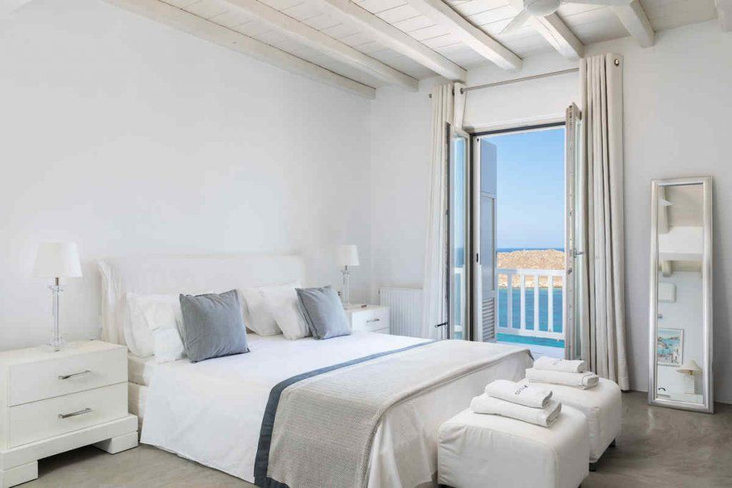 bedroom with cozy bed and beautiful view of sea