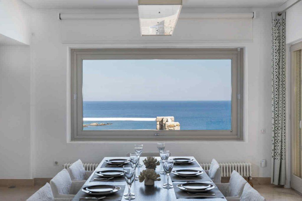 elegant dining room with candles and flowers, and out door view of sea