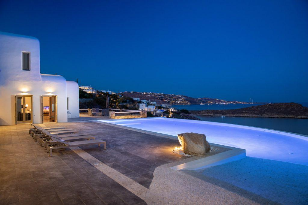 outdoor area with illuminated pool and lighted city