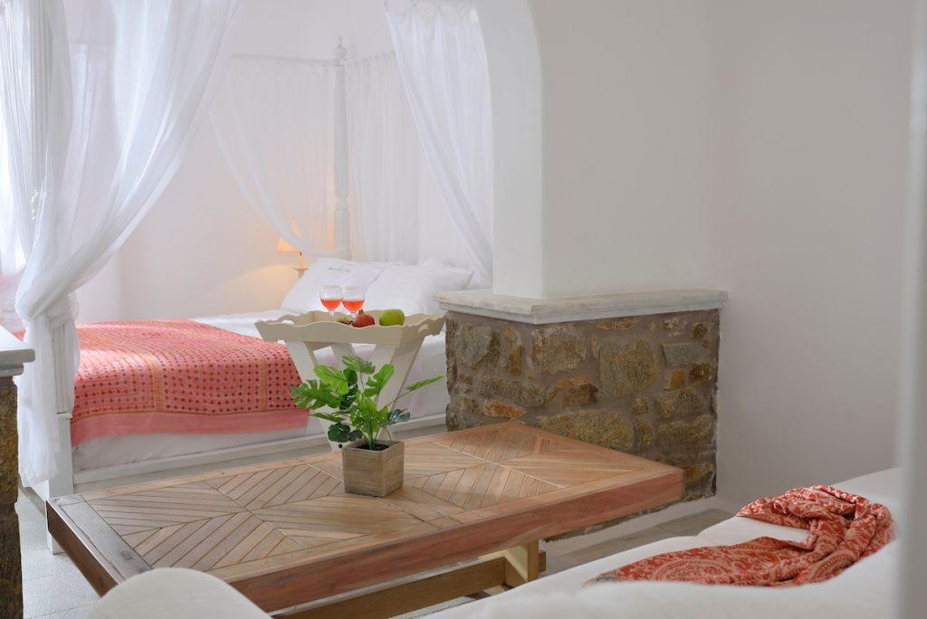 Villa Baha Ftelia Mykonos, 3rd bedroom, king size bed, pillows, table, sofa, blanket, plant, glasses, fruits