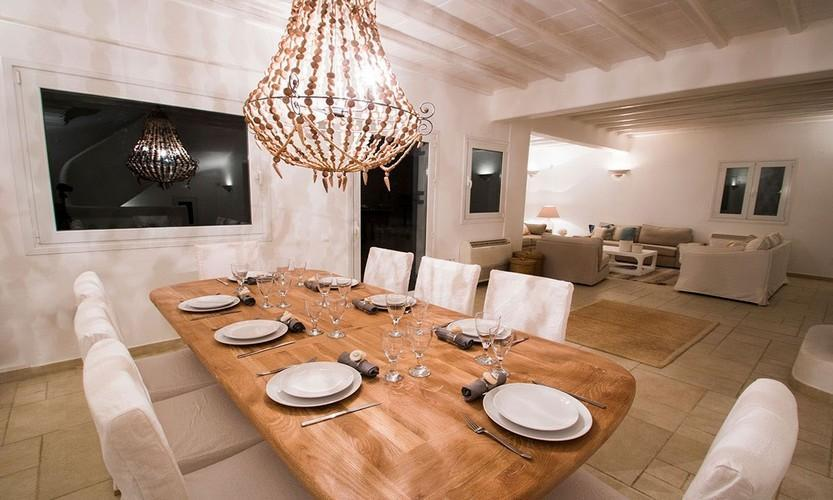 lavish wide illuminated living room and wooden set up dining table