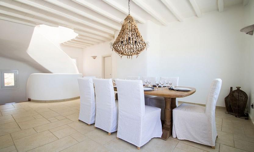 high ceiling dinning room with big oak table linen covered chairs and fancy chandelier