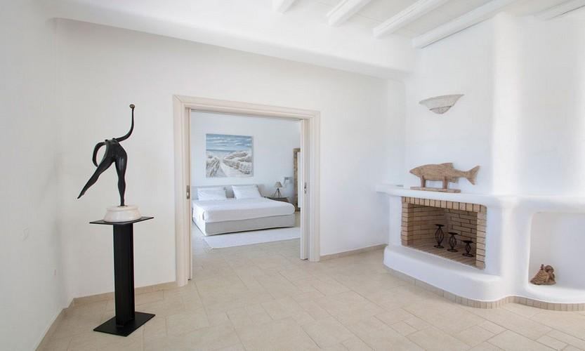 ivory marble tiled hallway with artistic figurine statute and embedded fireplace