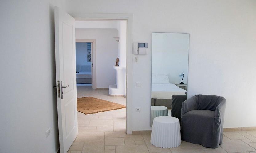 plain hallway with armchair small table and full length mirror