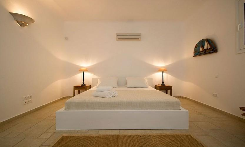 bright lightened and marble tiled bedroom with comfortable bed and air conditioning