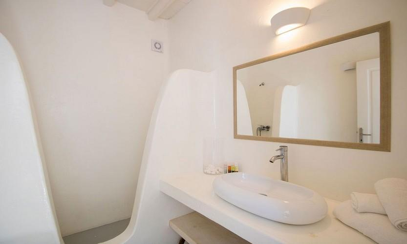 ivory tiled bright lighted bathroom with big sink and long wide mirror
