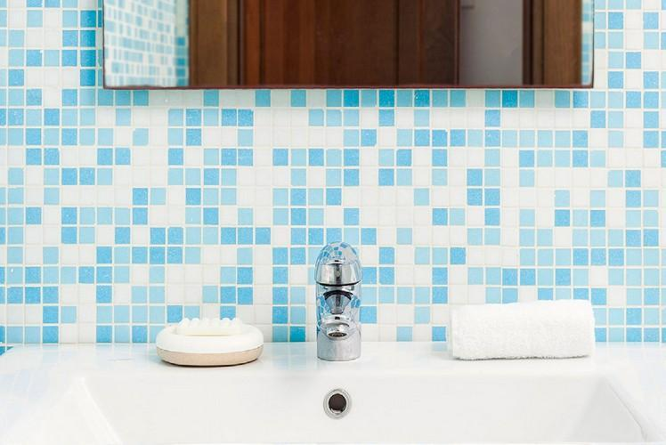 bathroom with blue tiled wall and soft towel