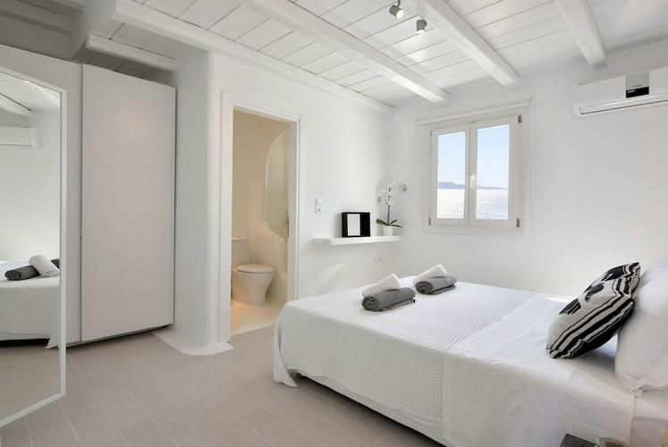 white wall bedroom with comfort bed and huge mirror