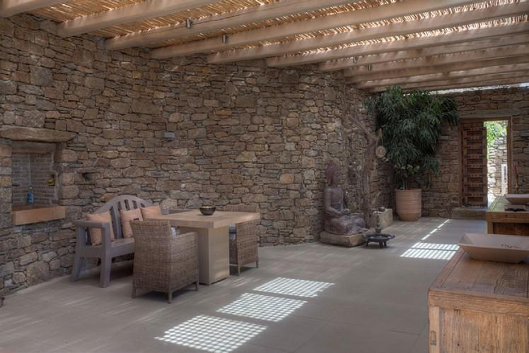 beautifully landscaped garden with stone walls and a wooden canopy