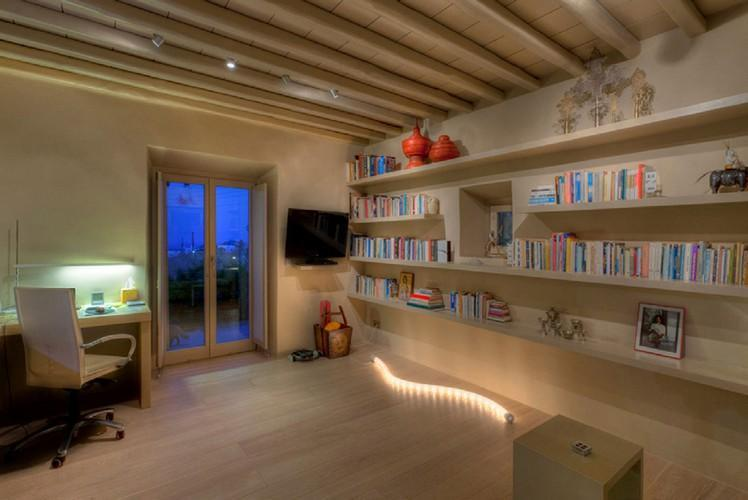 spacious room with a huge bookshelf and a lighted desk