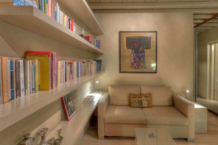 a bookshelf and a comfortable white couch ideal for enjoying reading a good book