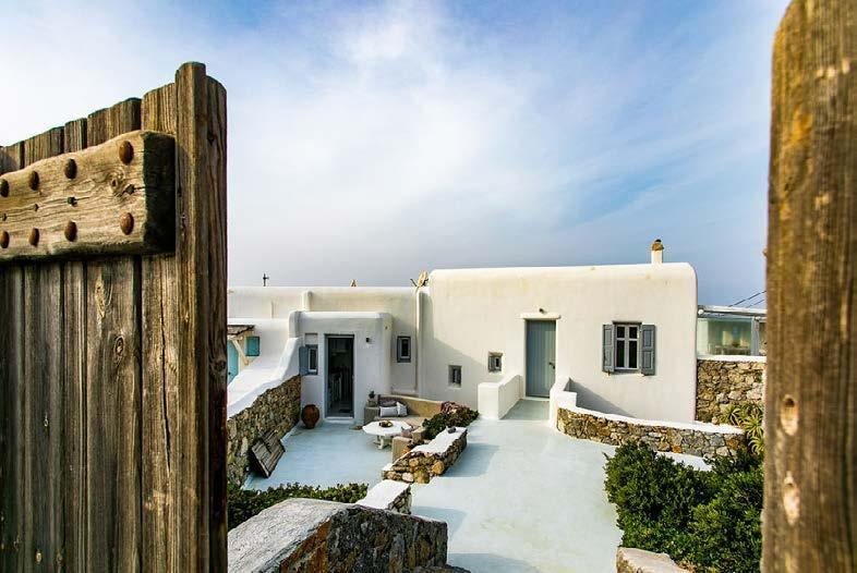 outdoor area with white villa walls and wooden gate
