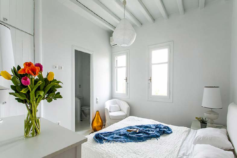 bedroom with comfort bed and corner white chair