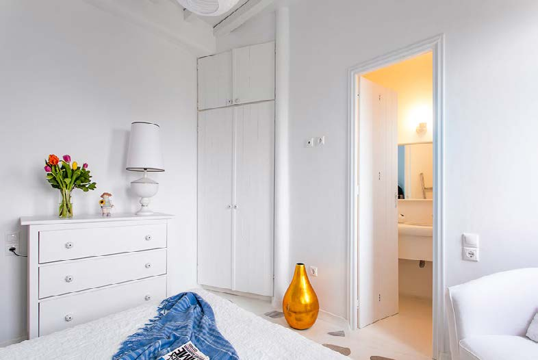 bedroom with gold vase and wooden white cabins
