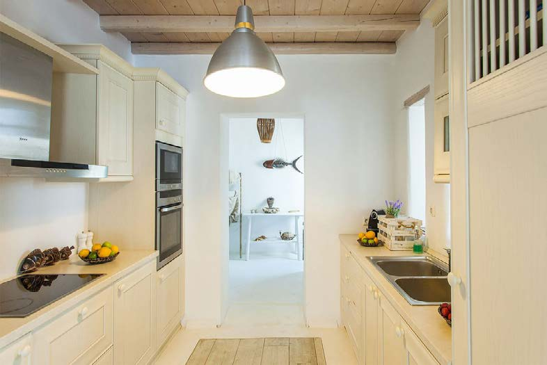 kitchen with wooden white cabins and chandelier