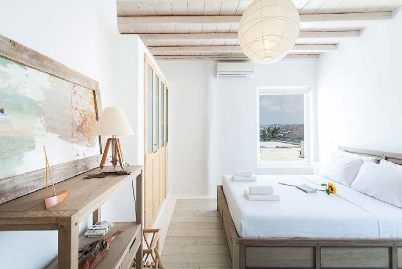 white wall bedroom with huge comfort bed and daylight from window