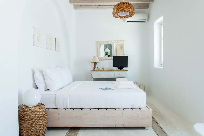 white wall bedroom with air condition and flat screen tv