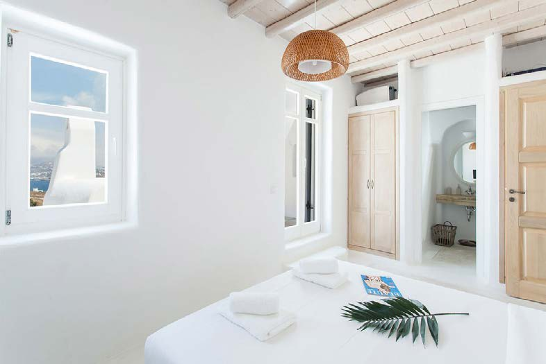 bedroom with wooden beige cabins and soft towels