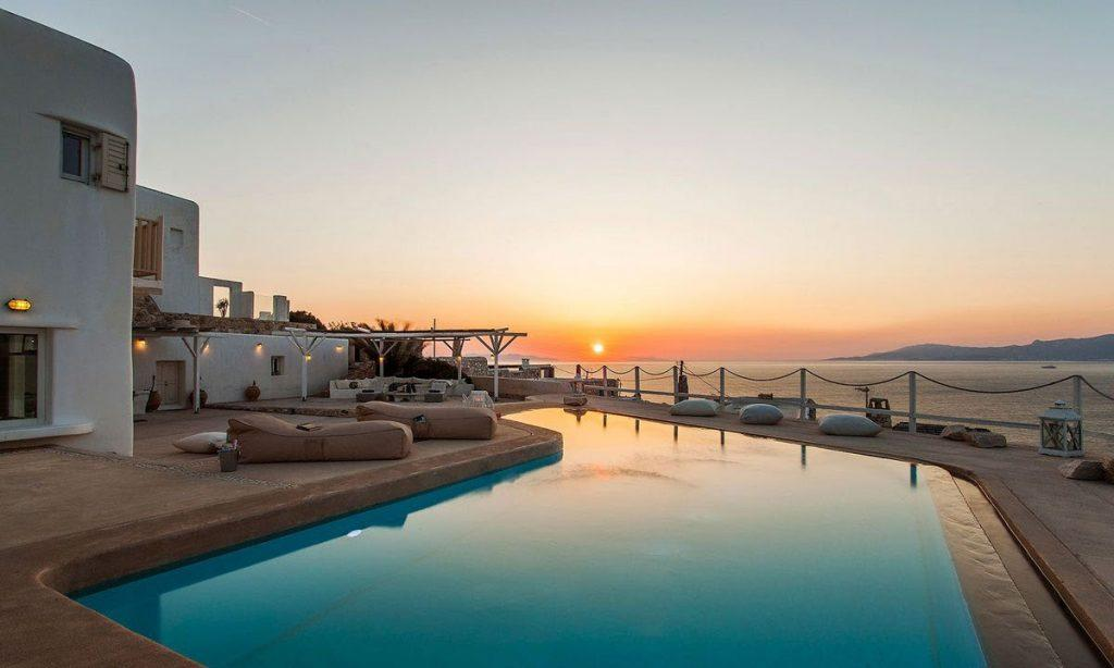 outdoor area with pool and beautiful sunset view