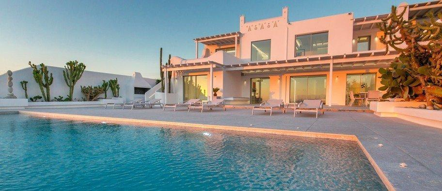 view of a luxurious white villa with a beautiful cactus garden