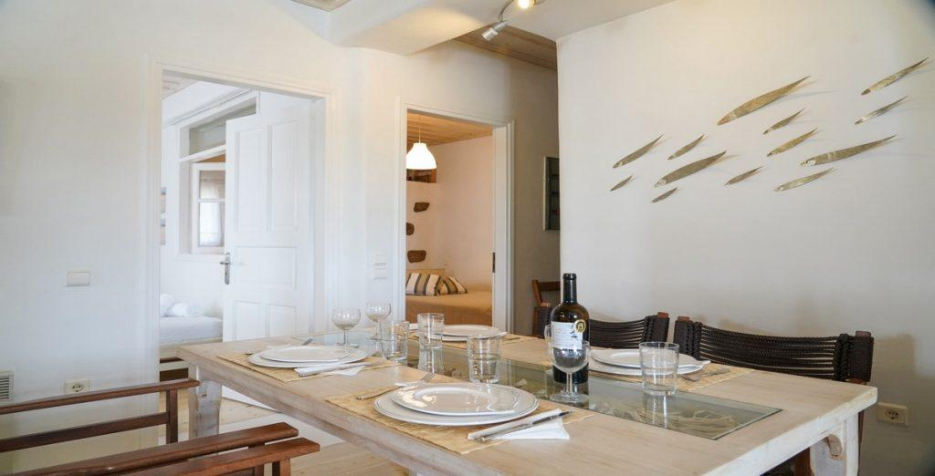 dining area with vine bottle on table and fish symbol on the wall