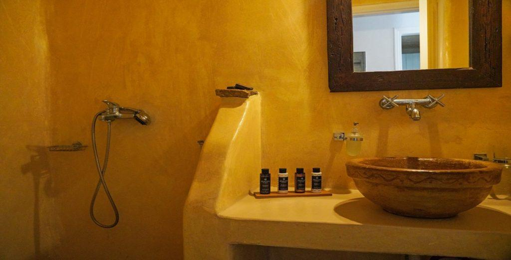 yellow wall bathroom with shower and clay sink