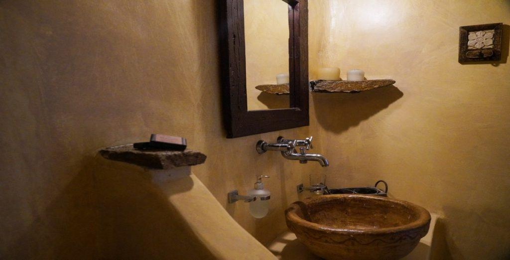 old designed bathroom with wooden mirror frame and clay sink