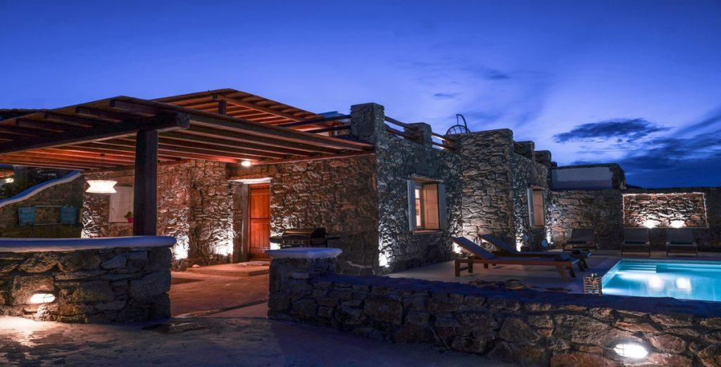outside of rocky villa with the porch and illuminated pool
