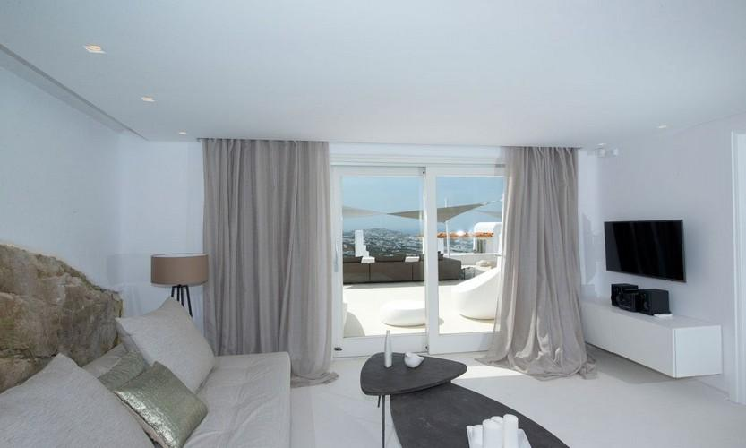 Villa_Antonia_07.jpg Tourlos Mykonos Living area, flat screen tv, curtains, table, candle, bed, pillows, lamp