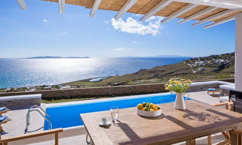 Villa_Apollo_13.jpg Choulakia Mykonos Outdoor Dining area, table, vase, chairs, flowers, pool, sea, sky, hill