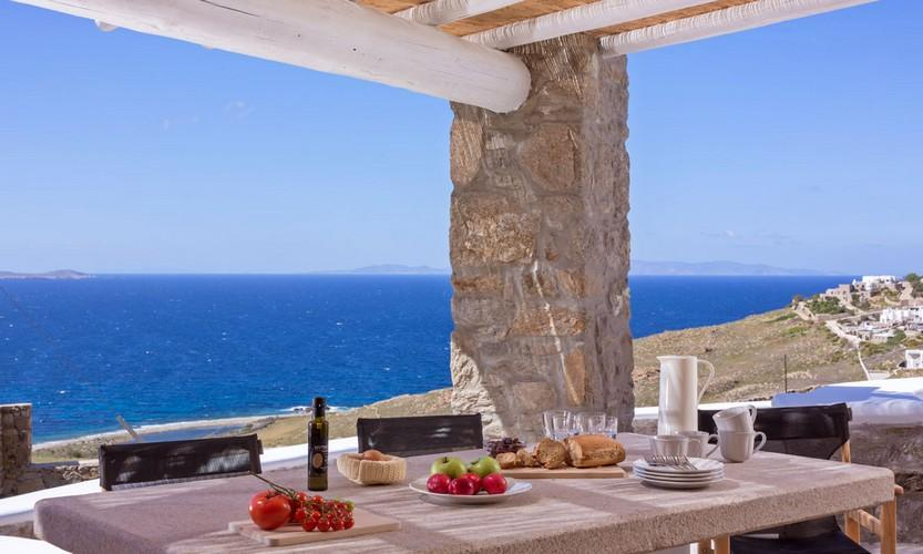 Villa_Apollo_17.jpg Choulakia Mykonos Outdoor Dining area, table, bottle, plate, fruits, sea, sky, horizon