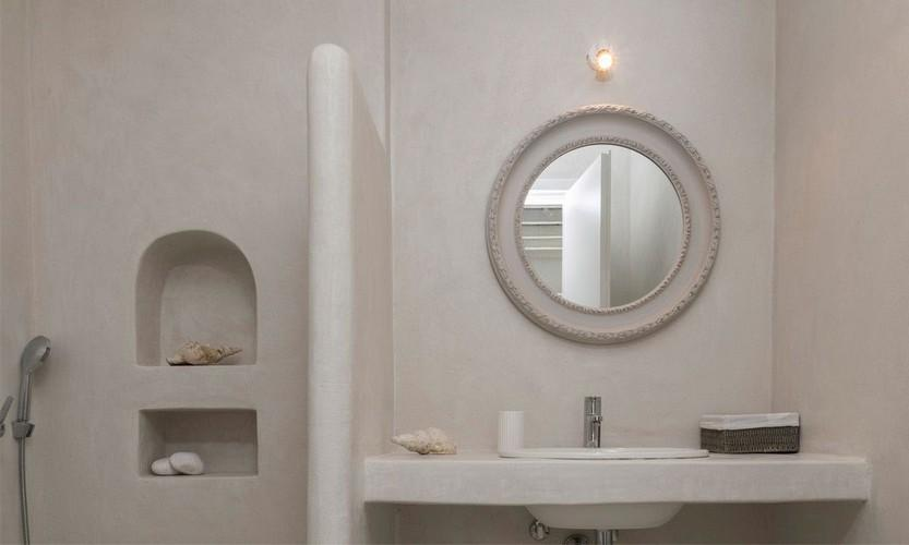 bathroom with unique round mirror and wall lamps