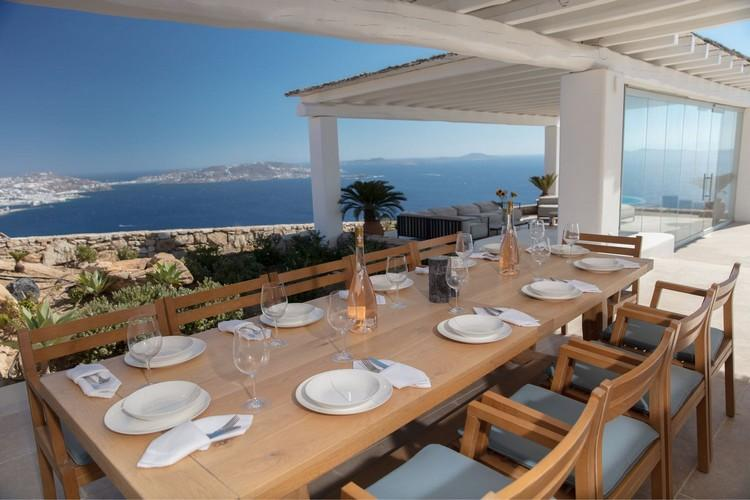 Villa_Nika_02.jpg Tourlos Mykonos Outdoor Dining area, table, chairs, plate, bottle, sea, sky