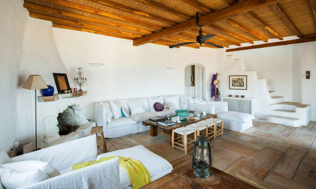 Villa Bob Agios Sostis Mykonos, living room, sofa, pillows, table, blanket, lamp, painting, stairs