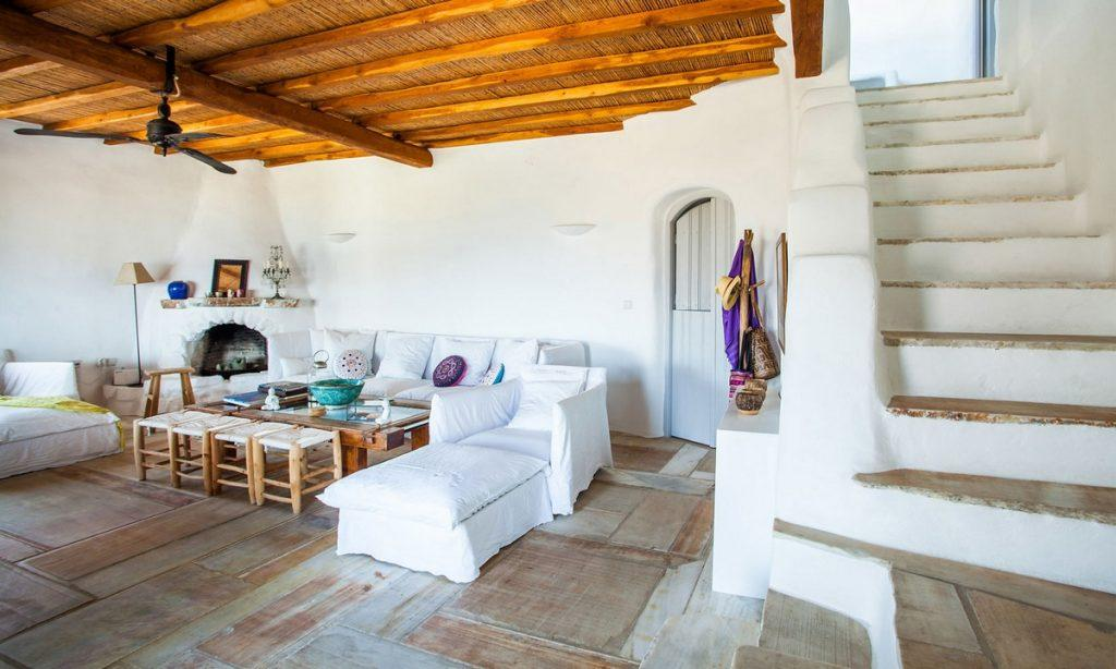 Villa Bob Agios Sostis Mykonos, living room, fireplace, sofa, pillows, stairs, chairs, lamp