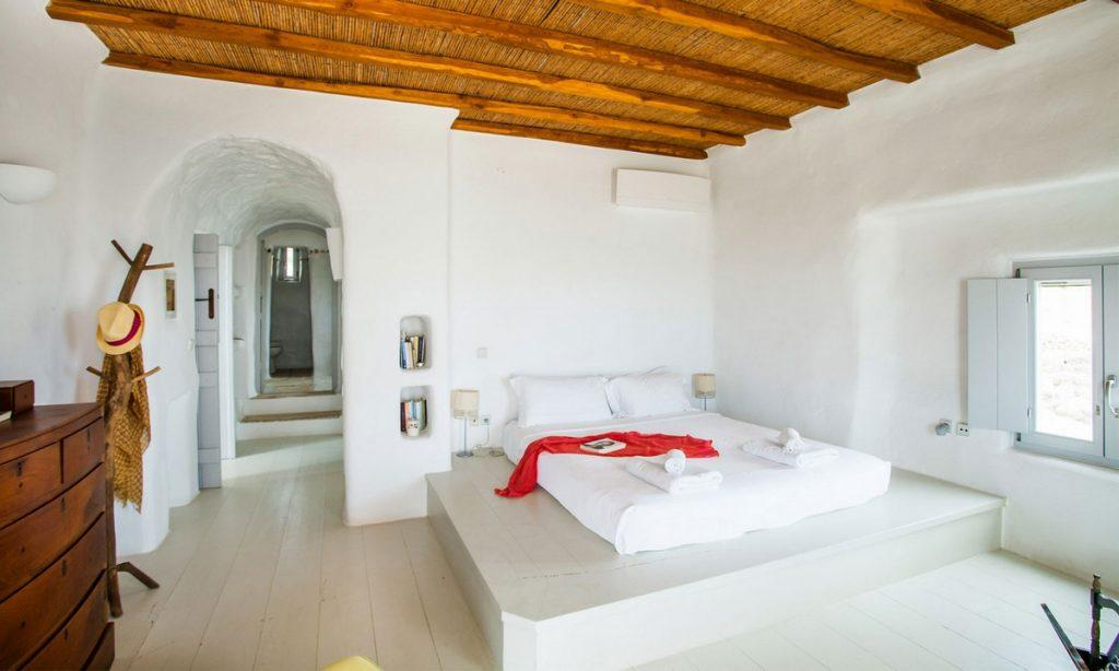 Villa Bob Agios Sostis Mykonos, 4th bedroom, king size bed, AC, pillows, lamps, nightstands, books, hat, window