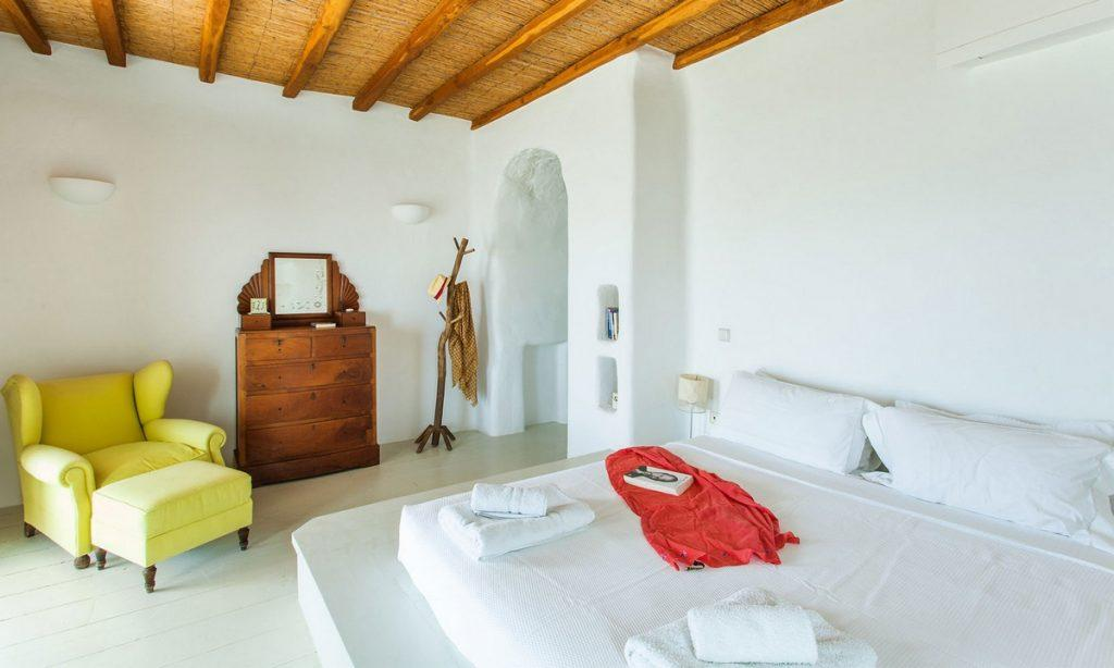 Villa Bob Agios Sostis Mykonos, 4th bedroom, king size bed, pillows, book, towels, robes, armchair, hat, mirror