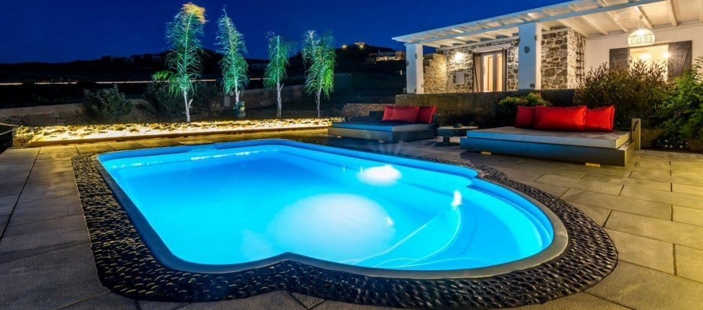outdoor area with illuminated pool and bed
