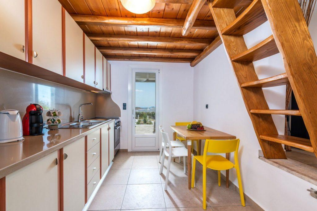 fully equip kitchen with dining table and wooden ceiling