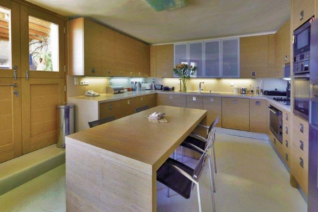 Villa Felicia Agios Lazaros Mykonos, kitchen, dining table, chairs, drawers, shelves, oven, sink, flowers, vase