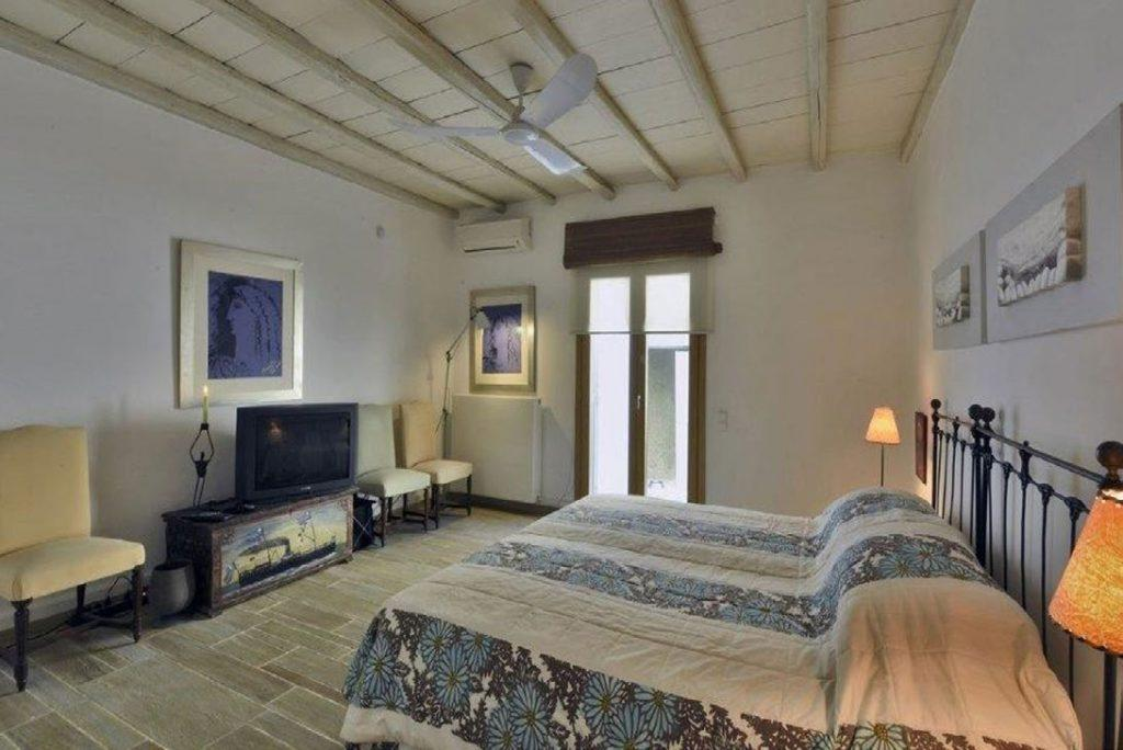 Villa Felicia Agios Lazaros Mykonos, 5th bedroom, double bed, TV, paintings, AC, chairs, pillows
