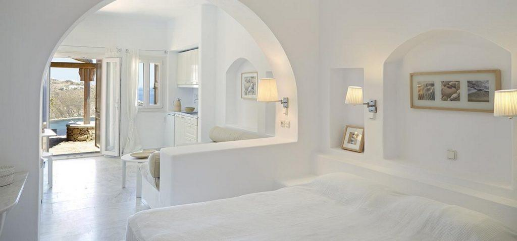white wall bedroom with comfortable bed night lamps above it and wall paints