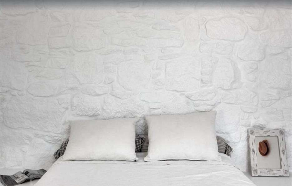 white stone bedroom walls with small mirror next to bed