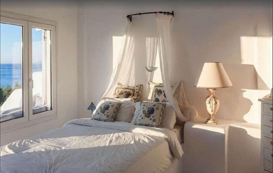 bedroom with curtains above bed and daylight from window