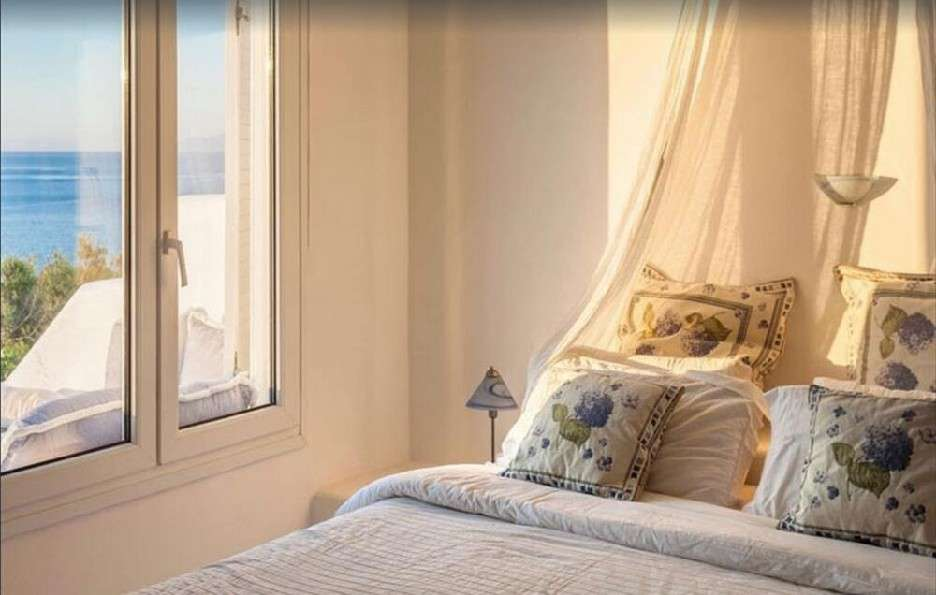 bedroom with unique designed pillows and curtains on bed