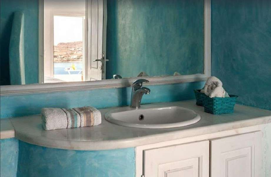 bathroom with blue walls and huge mirror