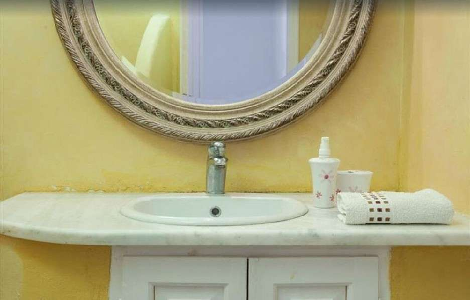 bathroom with round mirror and soft towels